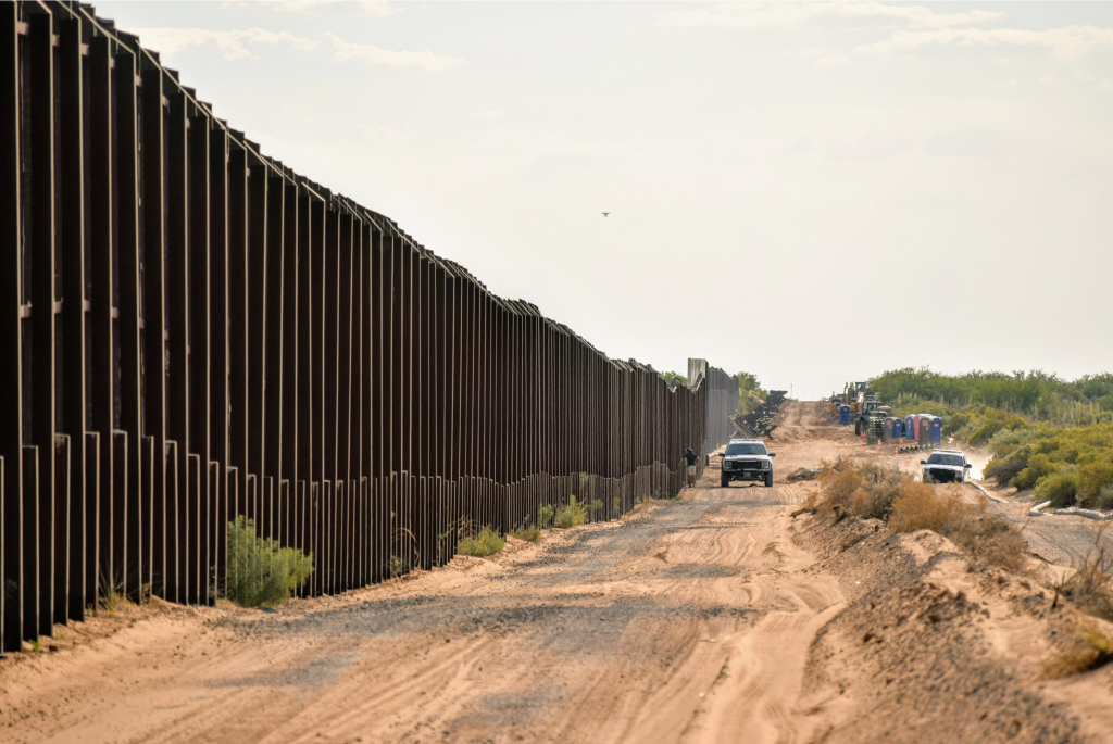 long view of the border wall between the usa and mexico with a couple trucks driving along side it