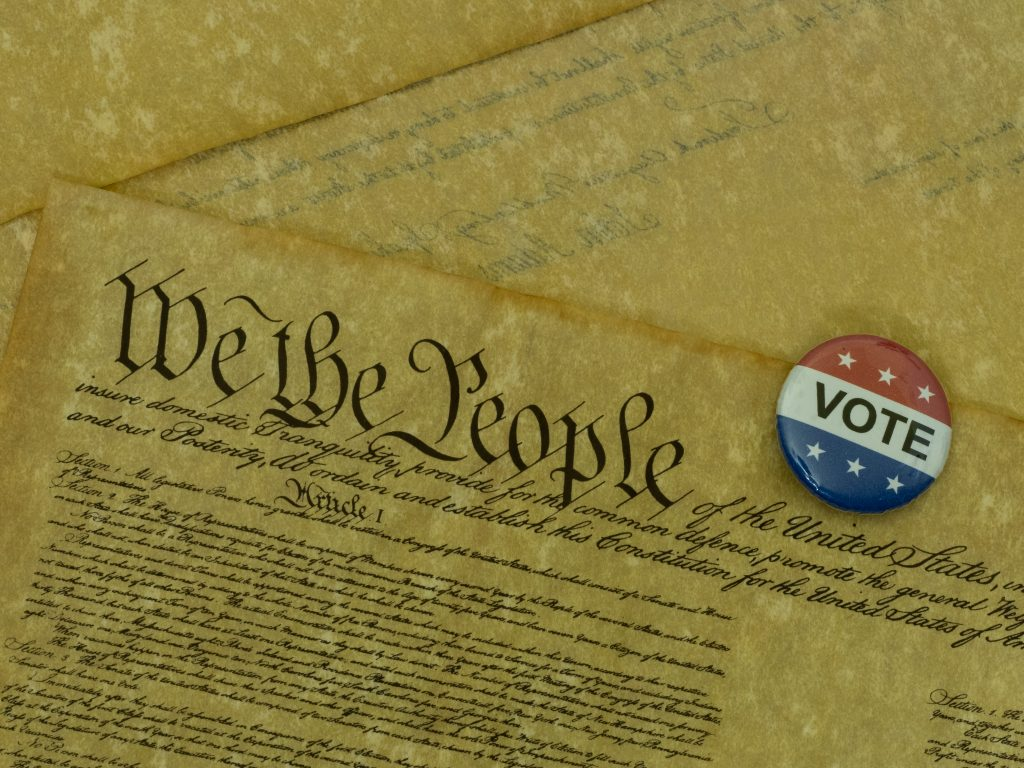 copy of the us consistution with a small vote button lying on it